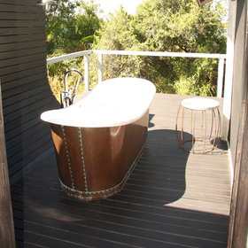A sliding door opens onto the veranda, where there is a clawfoot bathtub.