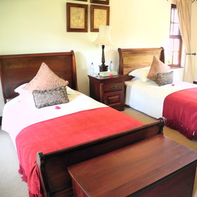 ... or twin beds, all dark wood and covered in rich red bedcovers and cushions.