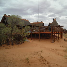 The thatched rooms at !Xaus Lodge are on top of red Kalahari dunes...