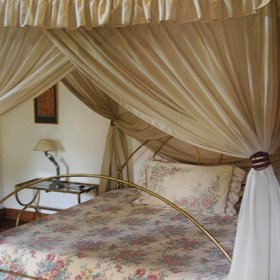 Each room has a four poster bed, draped with a mosquito net ...