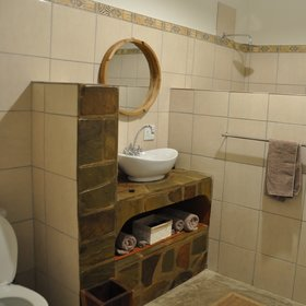The bathroom is open plan and decorated in neutral tones.