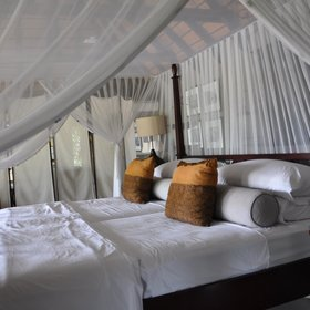 Adjoining the lounge is a huge bedroom with a four-poster king sized bed...