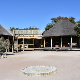 Sandy pathways lead to the camp's main area - a large, open-sided thatched building...