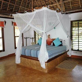 Inside you'll find a large double bed swathed in a mosquito net...