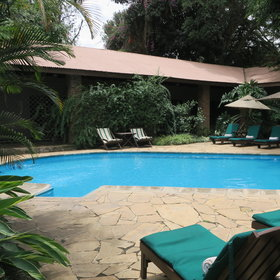 The swimming pool is tucked behind the main area and surrounded by sun loungers.