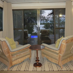 A seating area has comfortable chairs looking out to the deck...